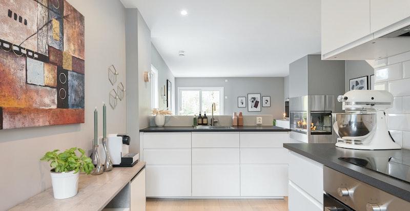 Flott kjøkken med ny innredning 2017. Det er åpen løsning mellom rommene men en noe forhøyet vegg bak kjøkkenbenken skaper en praktisk skjerming