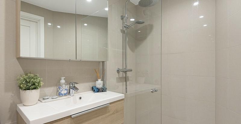 Lekkert flislagt bad med dusjnisje, vegghengt wc og plass for vaskemaskin