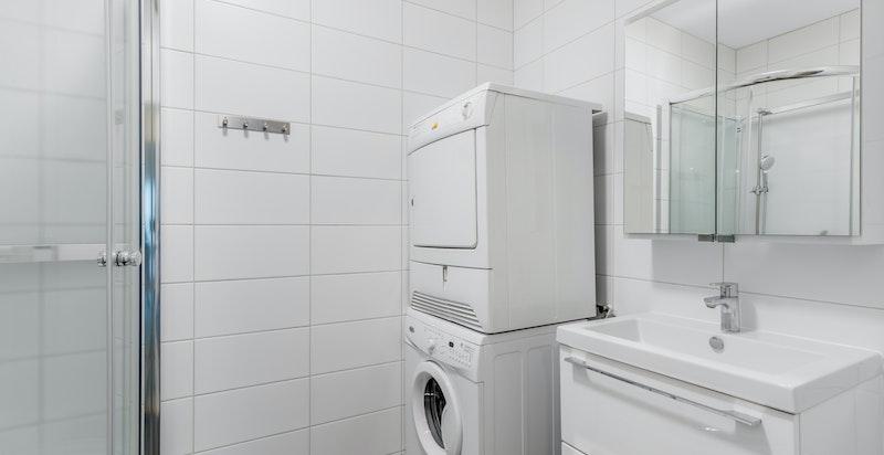 Delikat flislagt baderom med vaskemaskin og tørketrommel