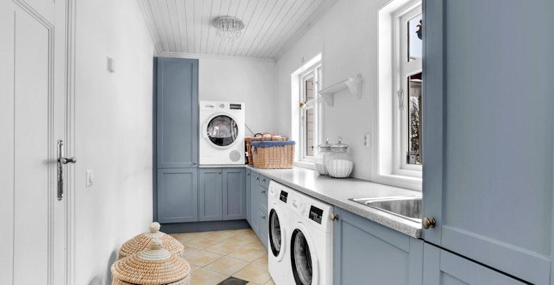 -Praktisk vaskerom innredet med skyllekum i stål i benkinnredning og opplegg til vaskemaskin/tørketrommel-
