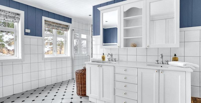 -Badet har flislagt gulv med varmekabler og flislagte vegger i brystningshøyde med malt panel over som gir en fin kontrast-