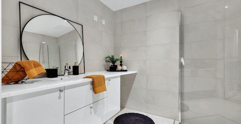 Hovedbadet har moderne baderomsinnredning i hvit utførelse fra HTH med oppbevaringsplass til baderomsartikler.
