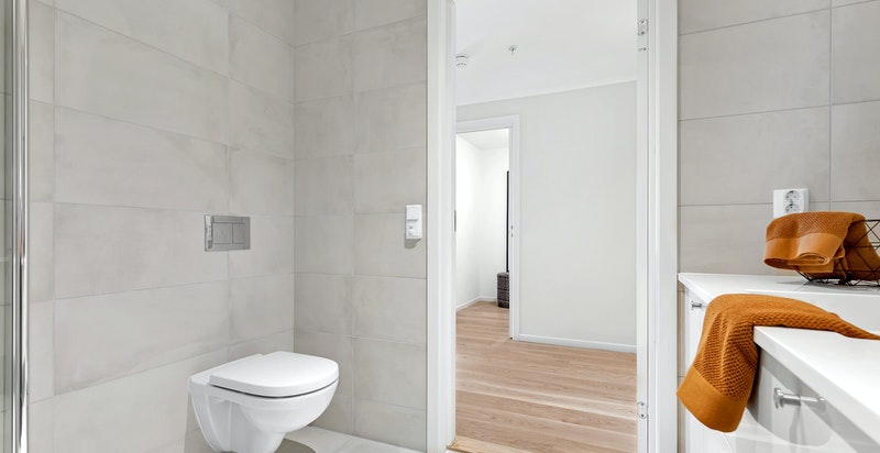 Vegghengt toalett og dusjnisje med innfellbare dusjvegger i herdet glass.