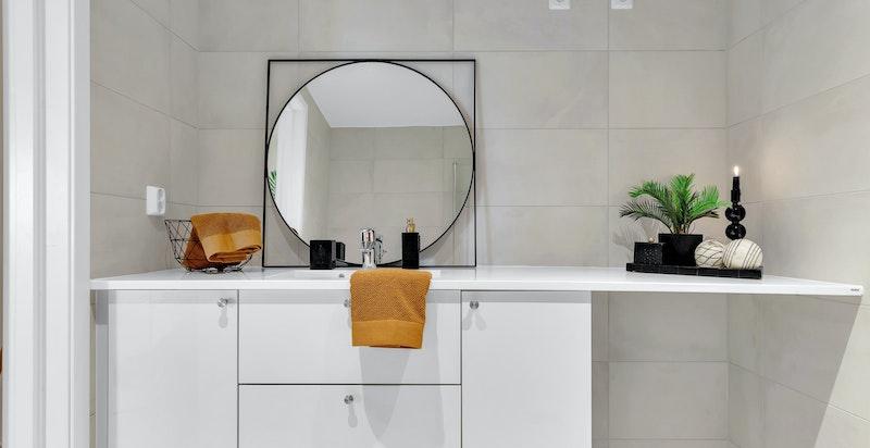 Vegg til vegg benkeplate og vask fra Kuma Marmor white gloss. Opplegg til vaskemaskin under benk.