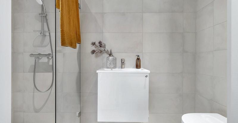 Moderne innredning, vegghengt toalett og dusjnisje med dusjvegg i herdet glass.