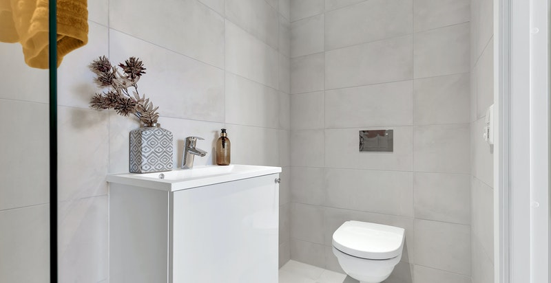 Bad 2 er også meget delikat og påkostet bad med sandfargede fliser, gulvvarme og downlightsbelysning.