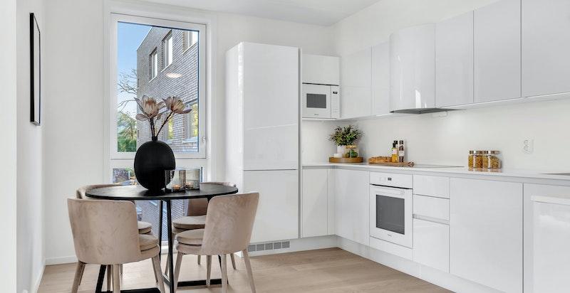 Påkostet og innholdsrikt kjøkken fra HTH i hvit høyglans kombinert med lekker hvit benkeplate i kompositt.