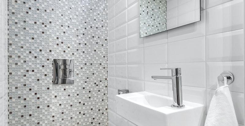 Separat toalettrom med veggmontert toalett, veggmontert servant med blandebatteri, ventil/avtrekk, speil med lys. Rommet ble overflateoppusset i 2015/-16