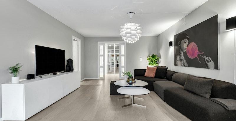 Stor og luftig stue med glass skyvedører ut mot gang