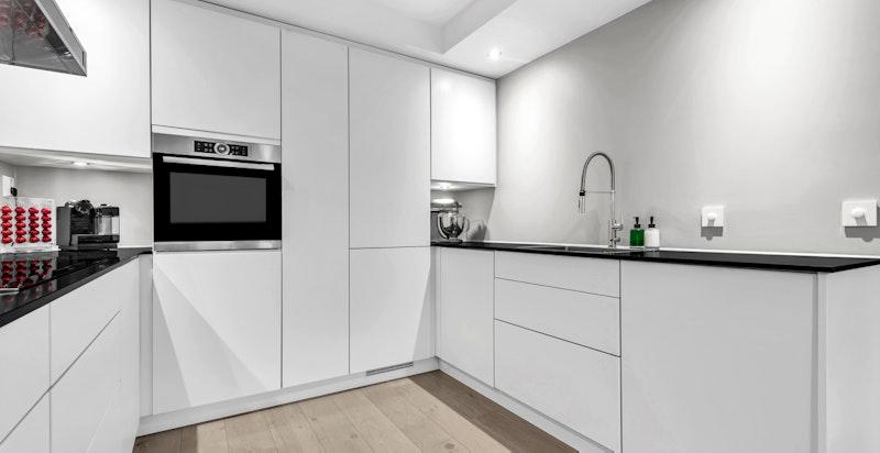 Meget pent kjøkken fra 2015/-16 bestående av glatte, matte fronter med push-open funksjon og automatisk åpner/lukker funksjon på oppvaskmaskin, avfallsskuff og kjøleskap. Kompositt benkeplater