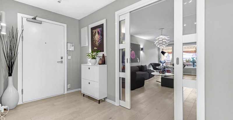 Overgang mellom hall/entré og stue. Lekre skyvedører med glass adskiller sosiale rom fra soverom, bad og wc