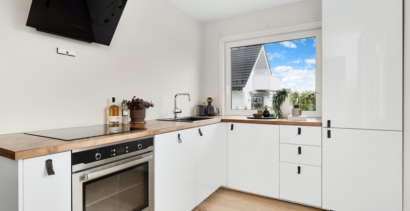 Pent kjøkken fra 2017. Det er vinduer på to sider og god oversikt over hage og inngangsparti