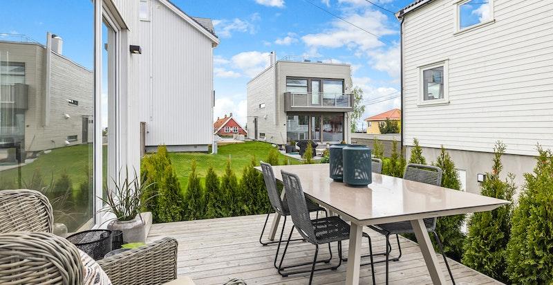 Hyggelig terrasseplatting ut fra stue med videre adkomst til hage
