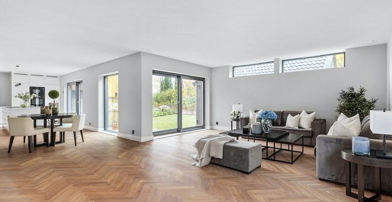 Stue/kjøkken med store vindusflater og utgang til terrasse