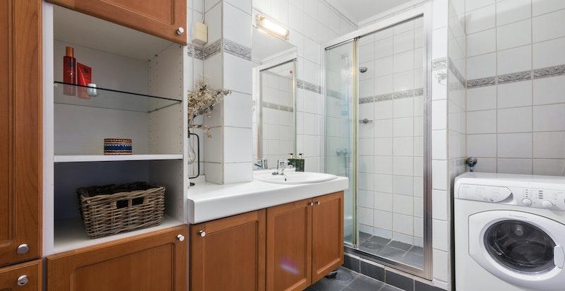 Flislagt baderom med opplegg for vaskemaskin, leiligheten har separat toalett i gangen