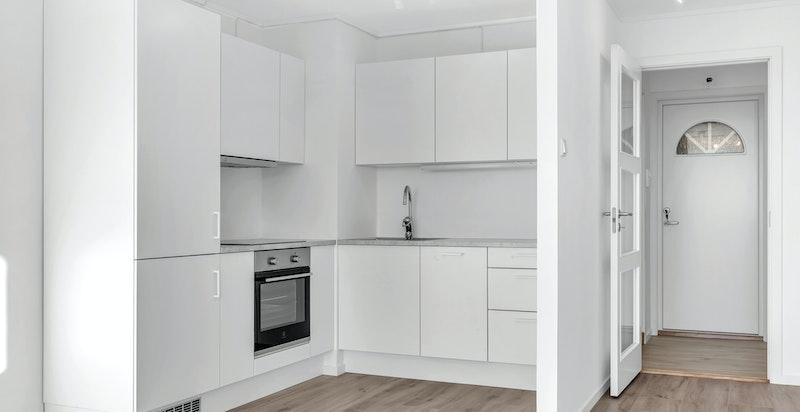 Kjøkkenet er praktisk designet i L-form med benkeskap, skuffeseksjon og overskap.