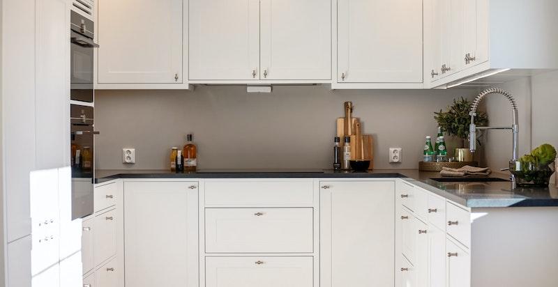 Kjøkkendesign fra På Millimeter'n. Fullstendig utstyr av integrerte hvitevarer. LED-spotter med dimmer i himling.