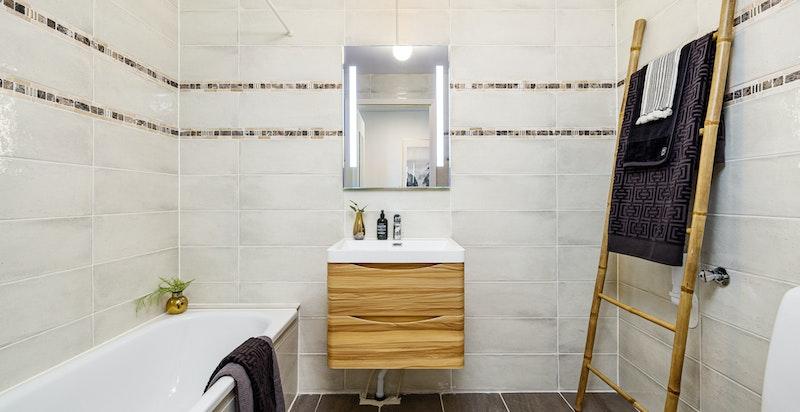 Pent og tiltalende baderom.  Eier har oppgradert badet i 2020 med nye fliser på vegger og gulv samt innmurt badekaret.