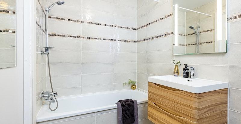 Ny baderomsinnredning og speil fra 2020. Det er opplegg til vaskemaskin på badet.