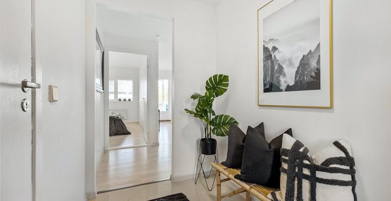 Entreen gir et godt førsteinntrykk av boligen med nymalte lyse flater og sandfargede fliser på gulv fra 2020.