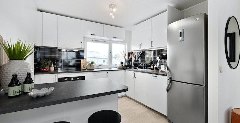 Nytt (2020) og innholdsrikt kjøkken med hvite glatte fronter kombinert med grå laminat benkeplate.