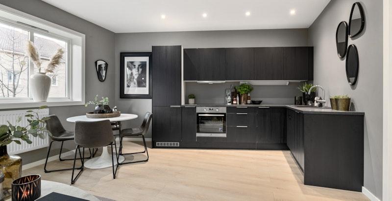Nytt, innholdsrikt og lekkert kjøkken fra HTH med sorte glatte fronter og laminat benkeplate.
