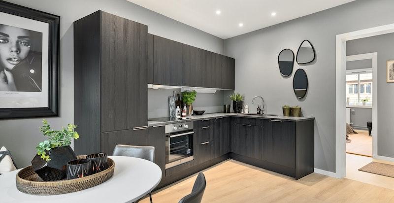 Kjøkkenet et praktisk designet i L-form med benke- og skapplass.