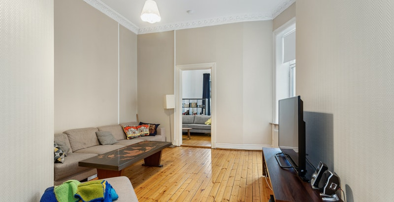 Enda en romslig stue/TV stue med inngang til ett av leilighetens fire soverom