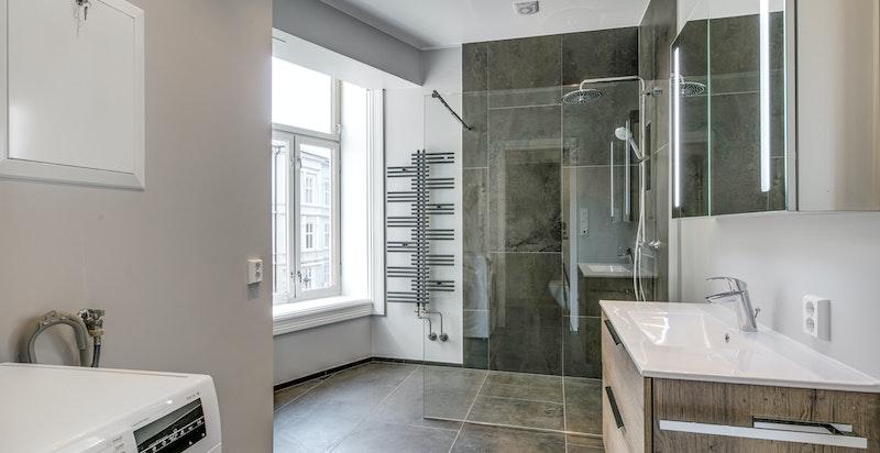 Badet er romslig med dusjnisje, servant og vaskemaskin