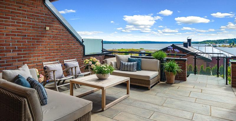 Fra terrassen ved inngangspartiet til denne flotte leiligheten med fantastisk nær sjøutsikt