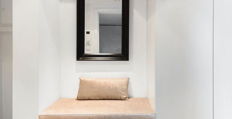 Representativt inngangsparti med integrerte skapløsninger fra gulv til tak, sittebenk  og speil