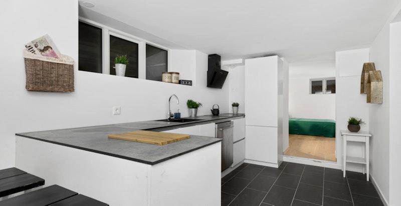 Moderne kjøkken fra Kvik med hvite glatte fronter og integrerte hvitevarer (hybel 2).