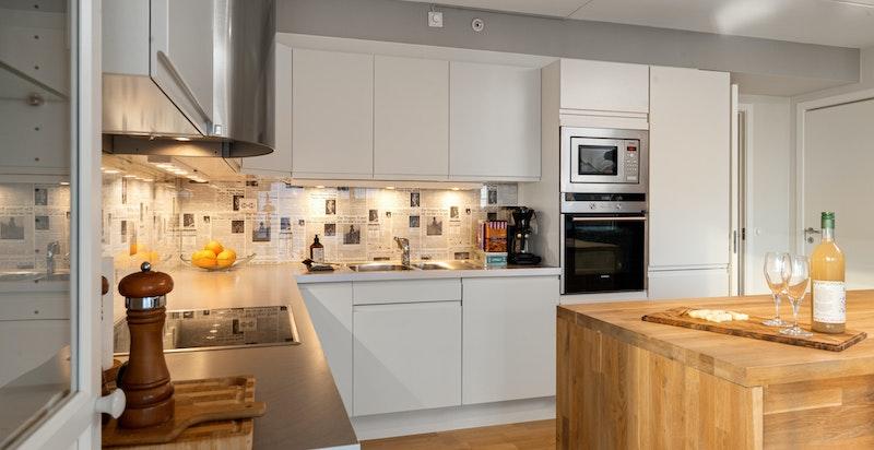 Lekkert oppgradert hjørnekjøkken med kjøkkenøy og rikelig med benkeplass og lagringsplass