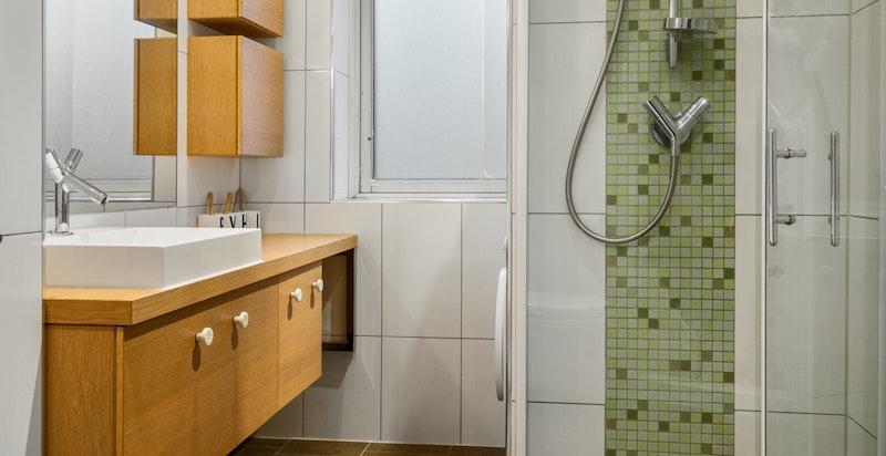 Pent og praktisk baderom med dusjnisje og servant.