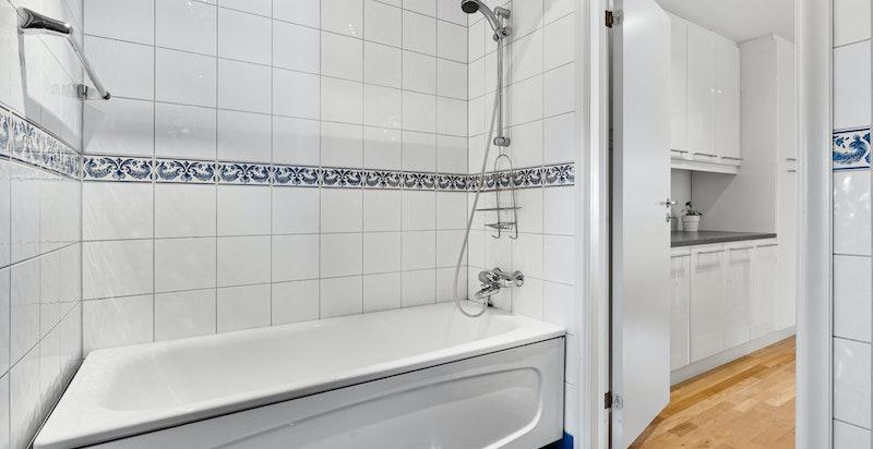 Hovedbadet er utstyrt med badekar med dusj, servant i skap, veggskap og toalett.
