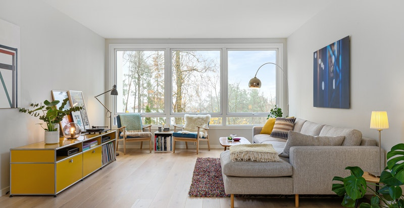 Lys og luftig stue med store vinduer ut mot grøntareal