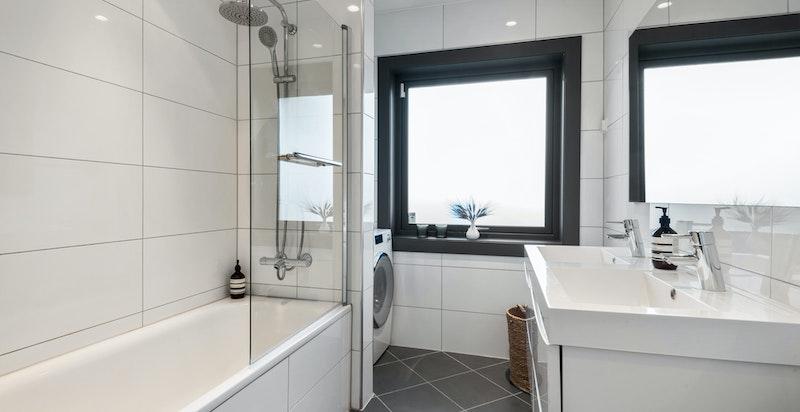 Delikat baderom med badekar og opplegg for vaskemaskin og tørketrommel.