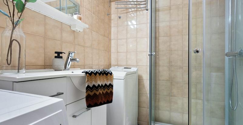 Eldre men funksjonelt baderom med dusjkabinett, servant og opplegg for vaskemaskin.