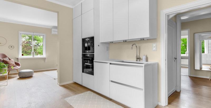 Innholdsrikt innredning med integrert stekeovn og induksjon koketopp, kaffemaskin, oppvaskmaskin, stekeovn og kjøl/frys. Avtrekksvifte til yttervegg.