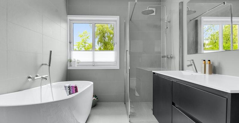Badet har vindu, varmekabler i gulv, veggmontert toalett, dusjhjørne med innfellbare dusjdører, to sluk, frittstående badekar