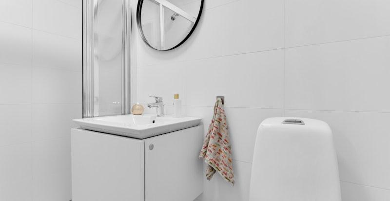 Bad/wc ved gang/trapp med varmekabler i gulv. Badet har toalett, dusjhjørne med skyvedør samt servant med underskap og blandebatteri