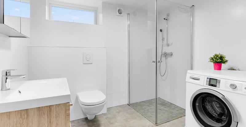 Delikat bad i kjeller som inneholder veggmontert toalett, dusjhjørne med innfellbare dusjdører, elektrisk avtrekksvifte, servant med underskap og blandebatteri, samt opplegg til vaskemaskin. Badet ble bygget i 2017/2018
