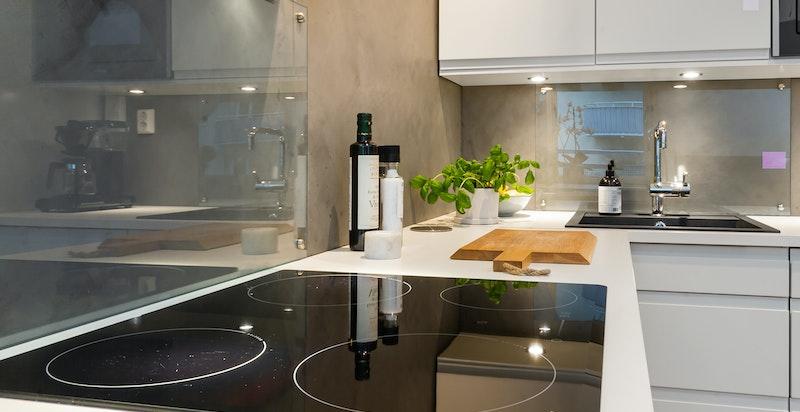 Kjøkkenet har integrerte hvitevarer og frittstående avtrekksvifte.