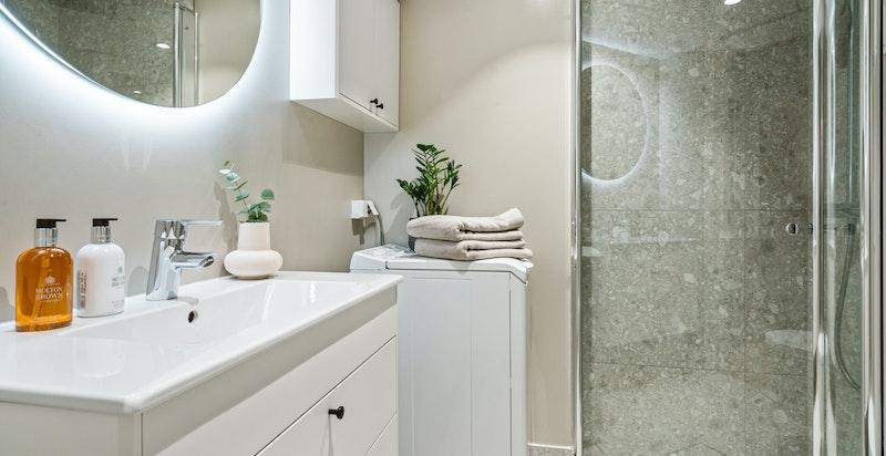 Svært delikat og nyere baderom med toalett, dusj, servant og opplegg for vaskemaskin.