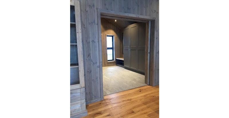 Bildet viser veggfarge beis, standard flis gulv, samt garderoben viser standard farge på innredning kjøkken og bad