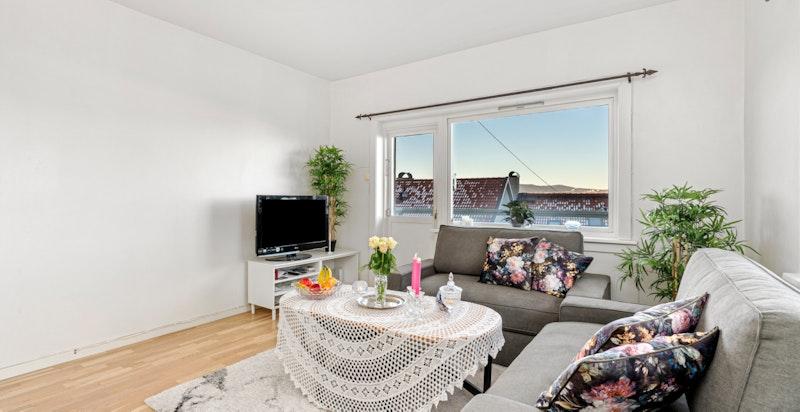 Romslig stue med god plass for salong og tv på medieveggen.