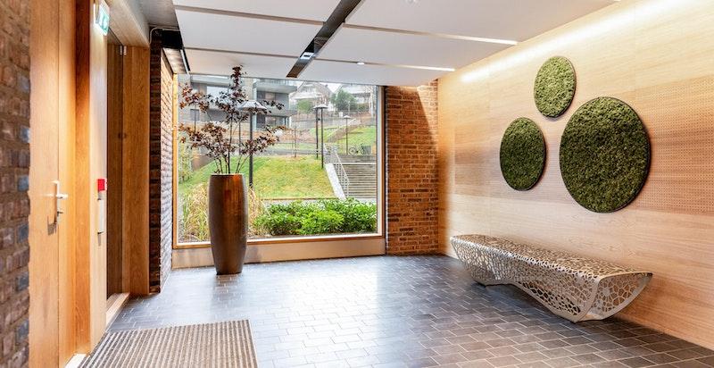 Det er moderne og flotte fellesfasiliteter i sameiet. Inngangsparti med utsmykking på vegger og skulpturell benk.