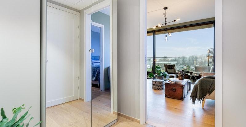 Entré sett mot stue. Det medfølger en dobbel speilgarderobe som gir godt med lagringsplass.
