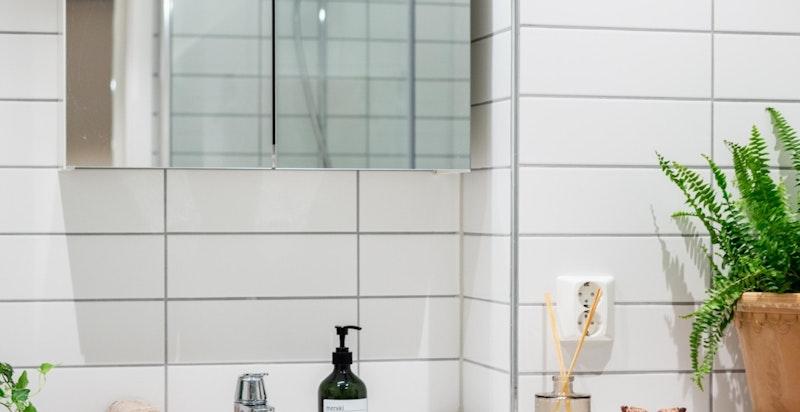 Badet har mørke grå gulvfliser, hvite veggfliser med tidløs innredning som gir et stilrent og moderne uttrykk.