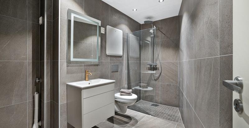Lekkert flislagt baderom med romslig dusjnisje